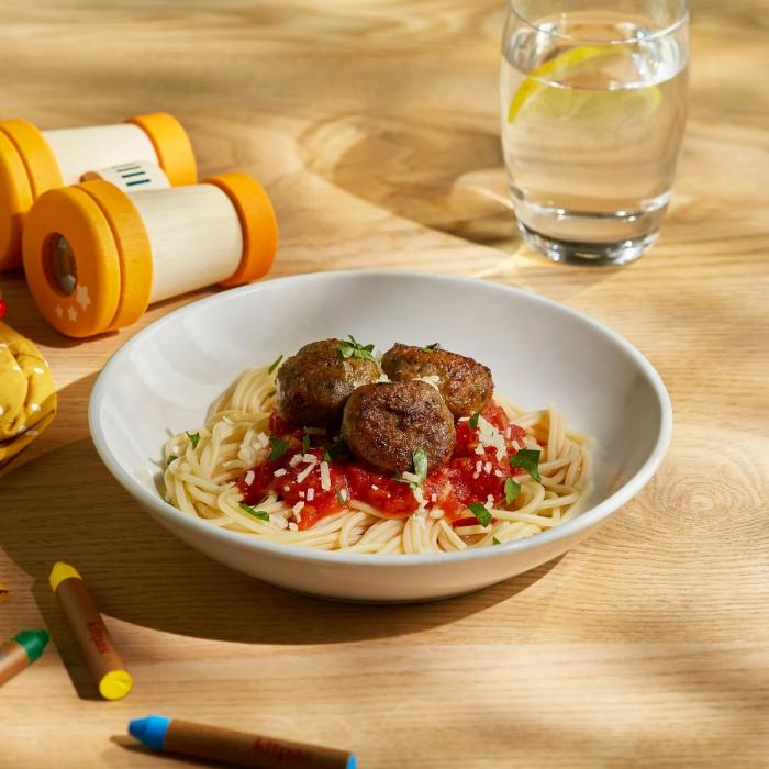 A bowl of spaghetti and meatballs surrounded by crayons and toys